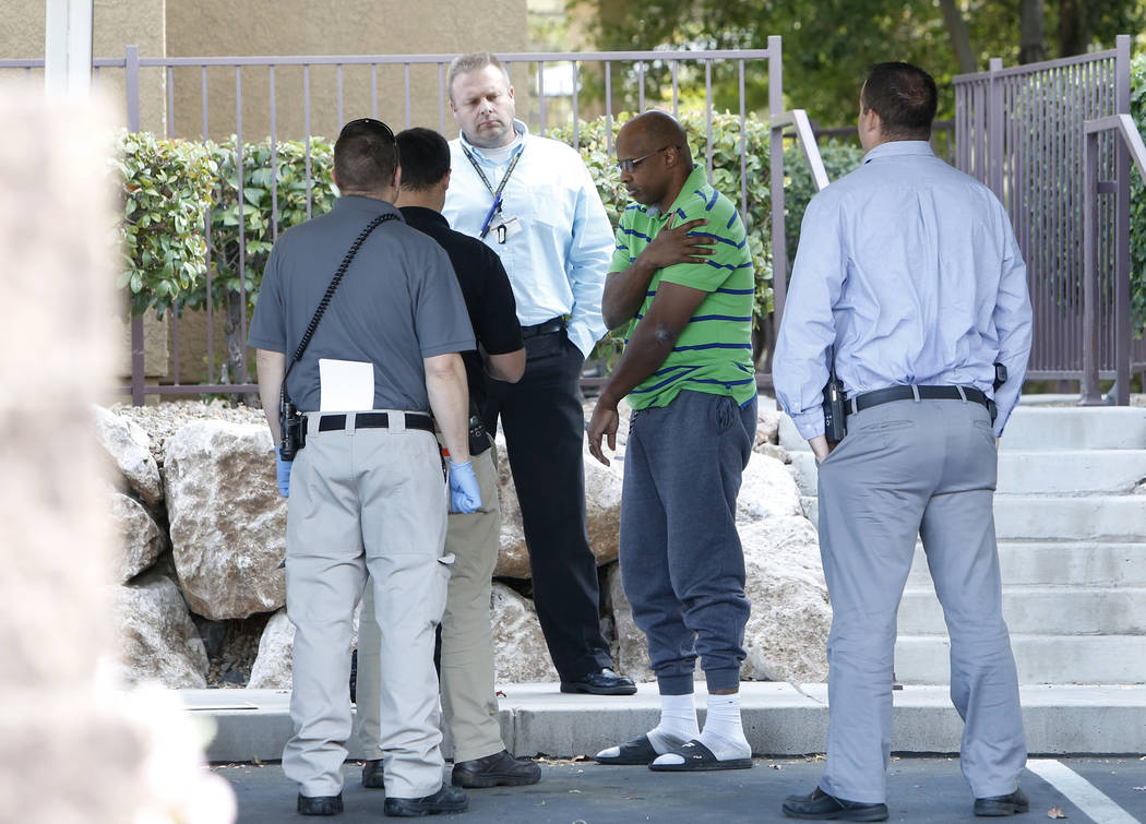 Henderson detectives talk to a man inside an apartment complex in the 900 block of Seven Hills Drive where a juvenile was shot and hospitalized on Thursday, Nov. 2, 2017, in Henderson. Bizuayehu T ...