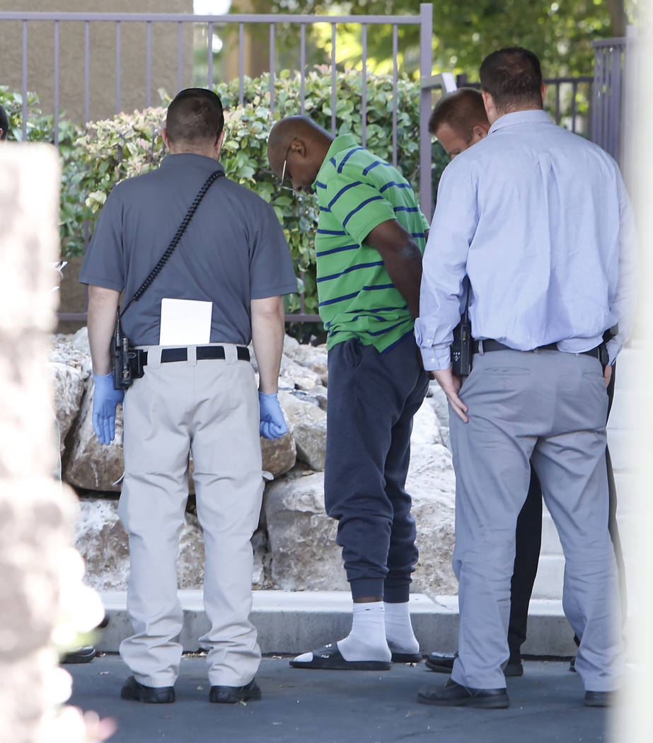 A Henderson police officer release a man from handcuffs inside an apartment complex in the 900 block of Seven Hills Drive where a juvenile was shot and hospitalized on Thursday, Nov. 2, 2017, in H ...