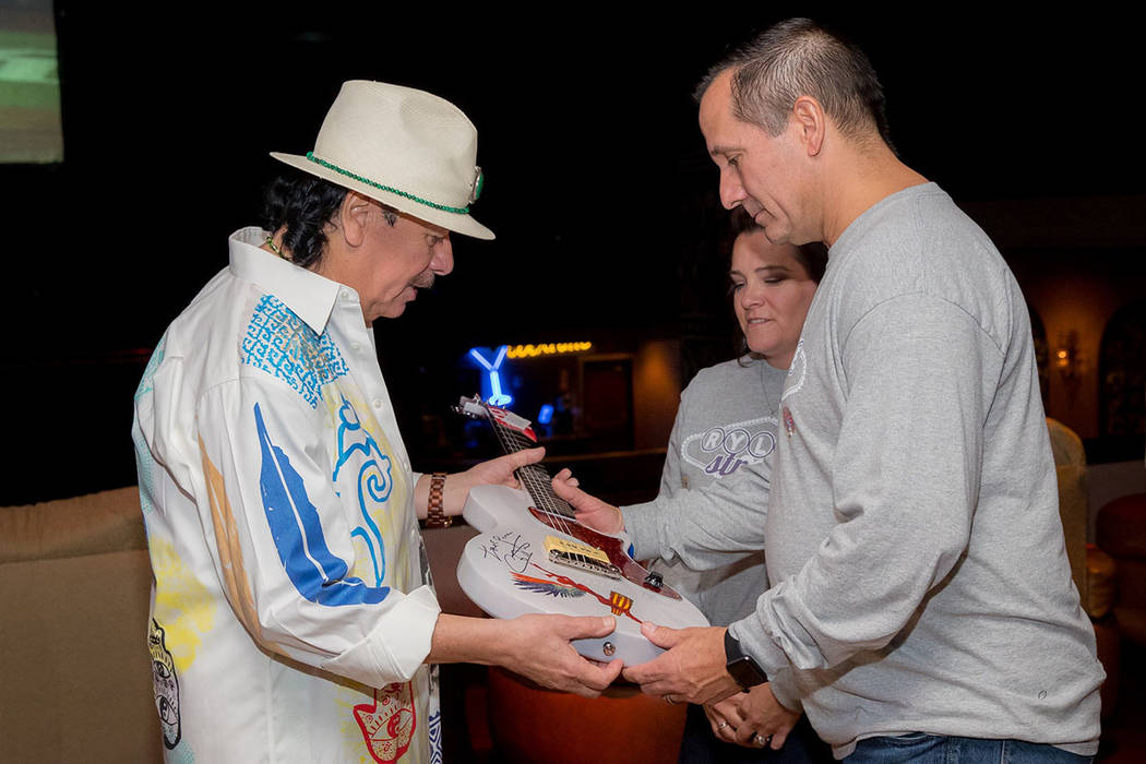 Carlos Santana presents a signed guitar to Richard and Kendra Golgart at House of Blues on Wednesday, Nov. 1, 2017. Their daughter Rylie Goldart, an 18-year-old student at Nevada State College, wa ...