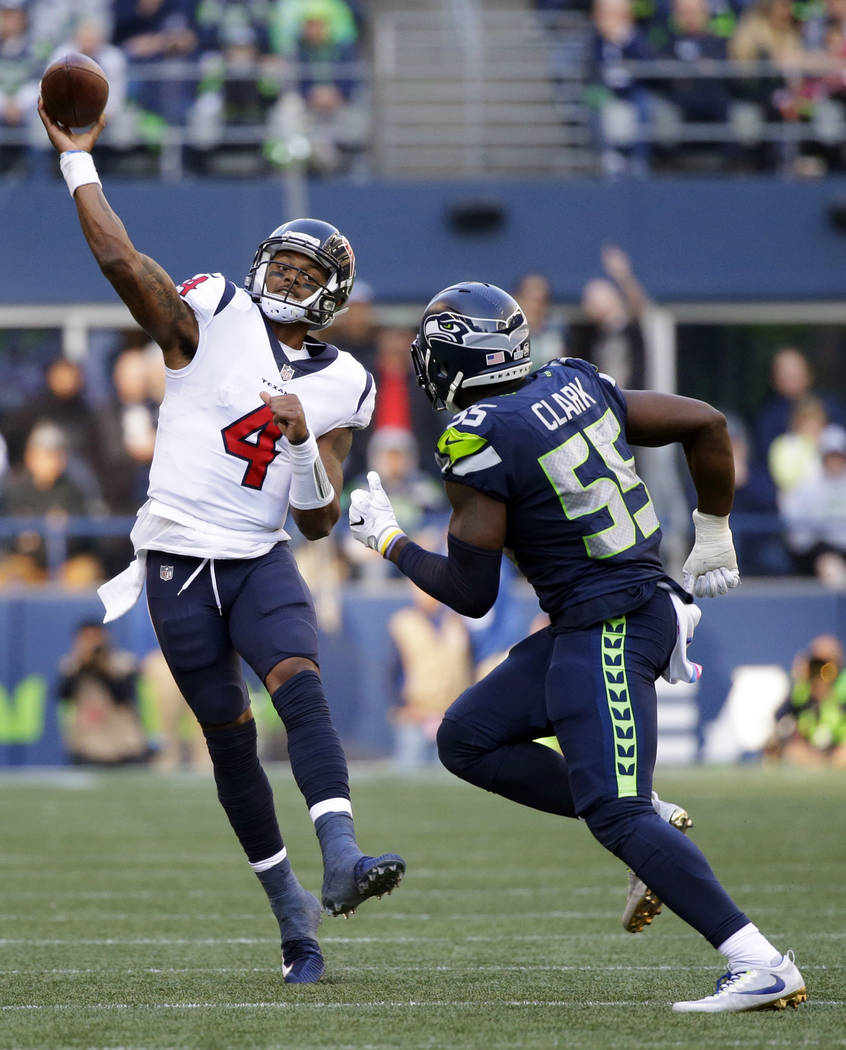 Houston Texans quarterback Deshaun Watson (4) passes to wide receiver Will Fuller over Seattle Seahawks defensive end Frank Clark, right, for a touchdown in the second half of an NFL football game ...