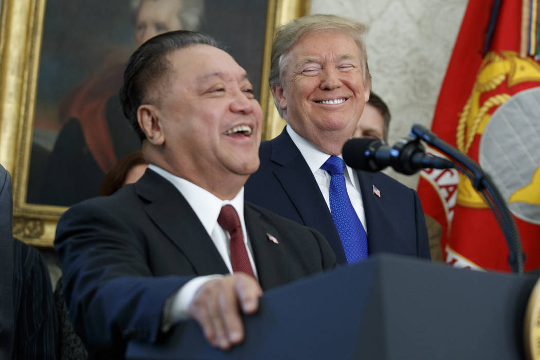 President Donald Trump smiles at Broadcom CEO Hock Tan during an event to announce that the company is moving its global headquarters to the United States, in the Oval Office of the White House, T ...