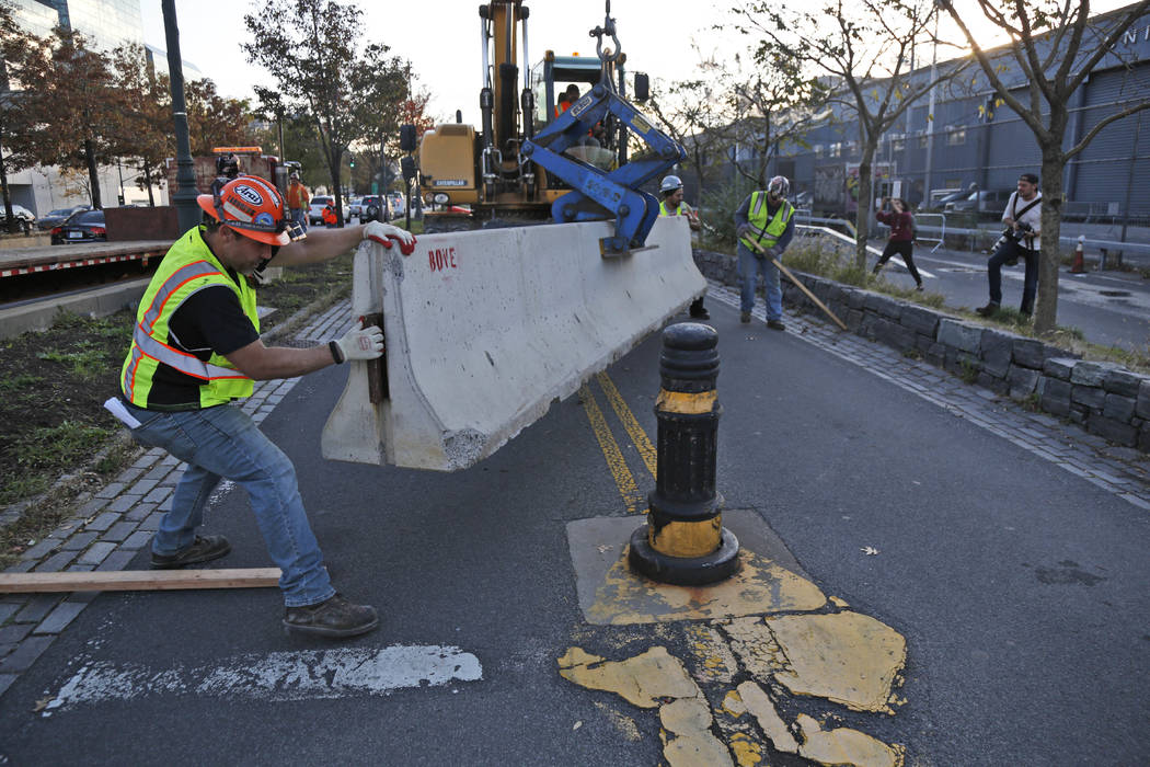Workers install a concrete barrier along the west side bike path in New York, Thursday, Nov. 2, 2017.  New York officials have started putting up additional concrete barriers at intersections, inc ...