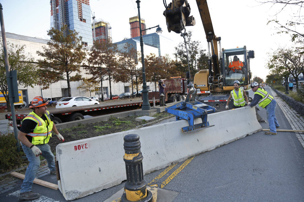 Workers install a concrete barrier along the west side bike path in New York, Thursday, Nov. 2, 2017. New York officials have started putting up additional concrete barriers at intersections, incl ...