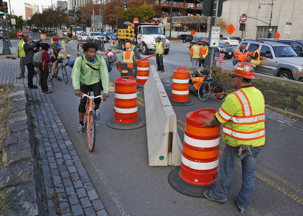Bicyclists make their way around a just installed concrete barrier along the west side bike path in New York, Thursday, Nov. 2, 2017. New York officials have started putting up additional concrete ...