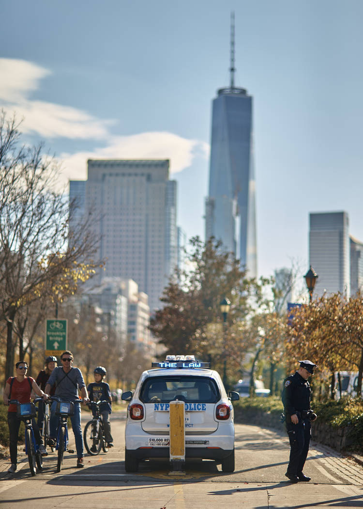 People bike as a police officer stands guard at the intersection of Houston and West streets on Thursday, Nov. 2, 2017, in New York. A man in a rented pickup truck mowed down pedestrians and cycli ...
