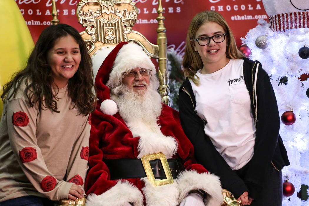 Alliyah Amezcua, 12, left, and Angelina Pretti, 12, right, get their photo taken with Santa Claus, center, during the 24th Annual Holiday Cactus Garden in Henderson, Tuesday, Nov. 7, 2017. Joel An ...