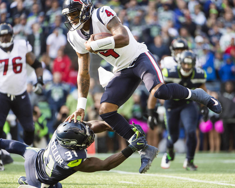 Oct 29, 2017; Seattle, WA, USA; Houston Texans quarterback Deshaun Watson (4) is tackled by Seattle Seahawks strong safety Kam Chancellor (31) during the first half at CenturyLink Field. Mandatory ...