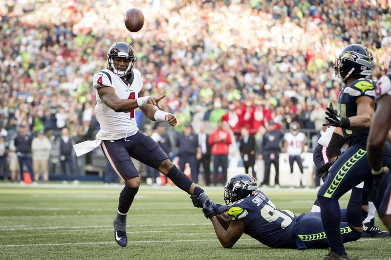 Oct 29, 2017; Seattle, WA, USA; Houston Texans quarterback Deshaun Watson (4) throws a touchdown pass as he is tackled by Seattle Seahawks defensive end Marcus Smith (97) during the second half at ...