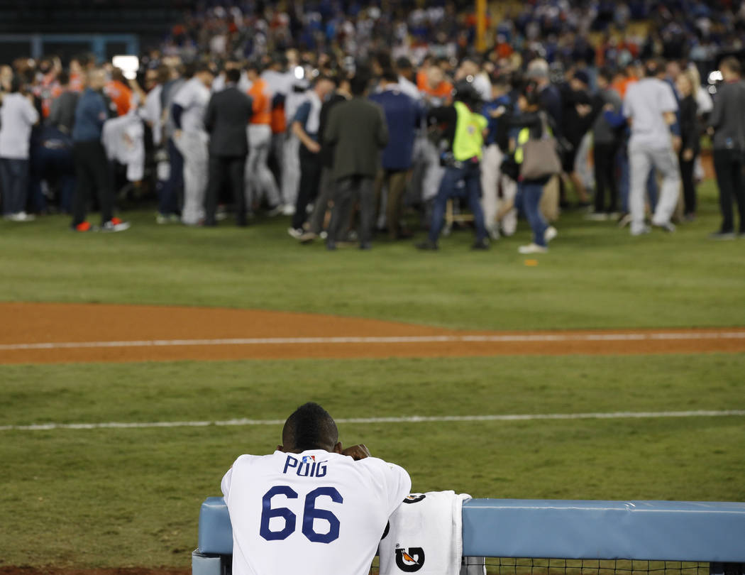 Los Angeles Dodgers right fielder Yasiel Puig watches as the Houston Astros celebrate their win in Game 7 of baseball's World Series Wednesday, Nov. 1, 2017, in Los Angeles. The Astros won 5-1 to  ...