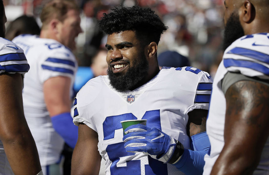 Dallas Cowboys running back Ezekiel Elliott smiles on the sideline after scoring a touchdown during the second half of an NFL football game against the San Francisco 49ers in Santa Clara, Calif.,  ...