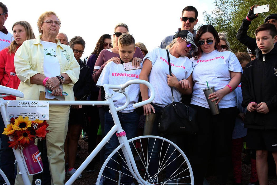 Carol Bradley, left, mother of Cara Cox and Cox's daughter Elizabeth Miller, second right, bow their heads during a moment of silence as they attend a ghost bike memorial ceremony for  Cox on Satu ...