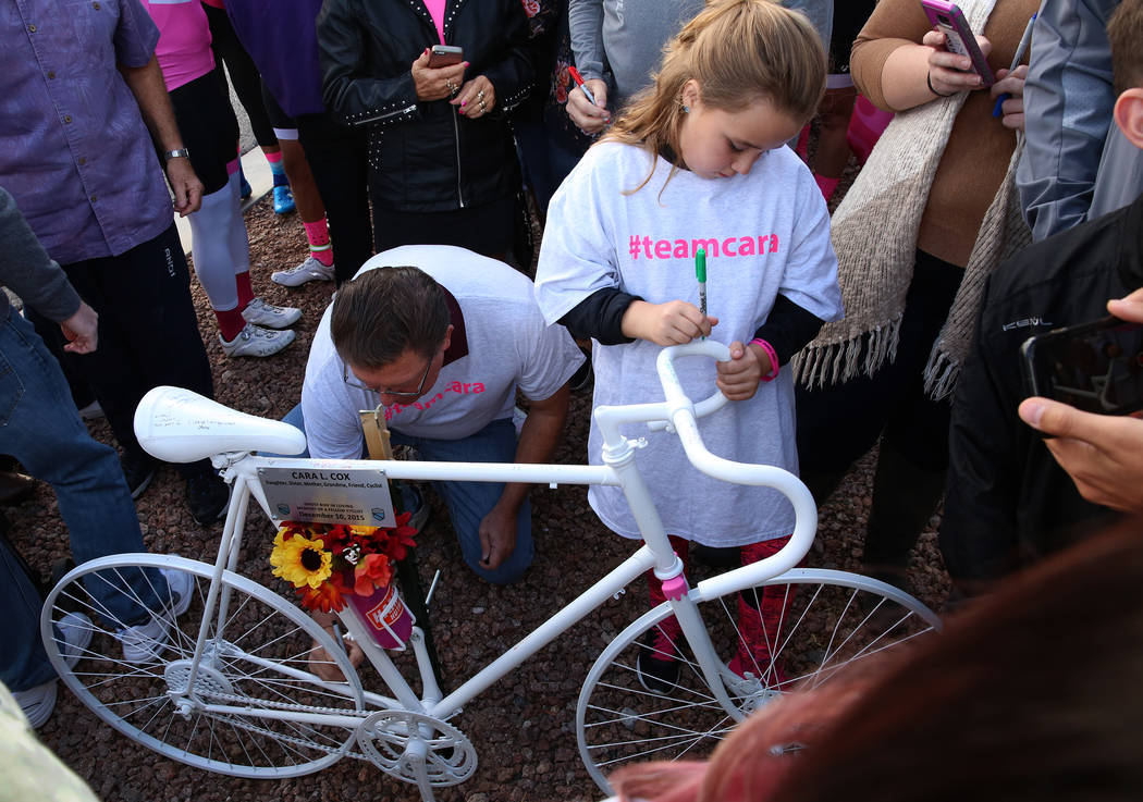 Addi Thompson, 9, writes a message on the ghost bike of Cara Cox during a ghost bike memorial ceremony on Saturday, Nov. 4, 2017, in Henderson. Cox was struck by vehicle while riding her bike on O ...