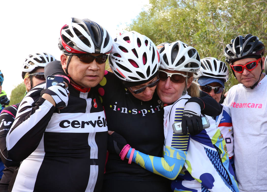 August Corrales, left, Gina Waymire, center, and Tracy Skelly comfort each other as they attend a ghost bike memorial ceremony for Cara Cox on Saturday, Nov. 4, 2017, in Henderson. Cox was struck  ...
