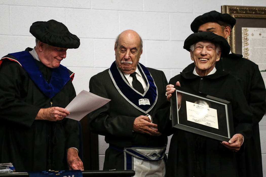 Edward Hall, 93, a WWII veteran and Pearl Harbor attack survivor, right, receives his high school diploma during a ceremony at the Masonic Memorial Temple in Las Vegas, Monday, Nov. 6, 2017. Joel  ...