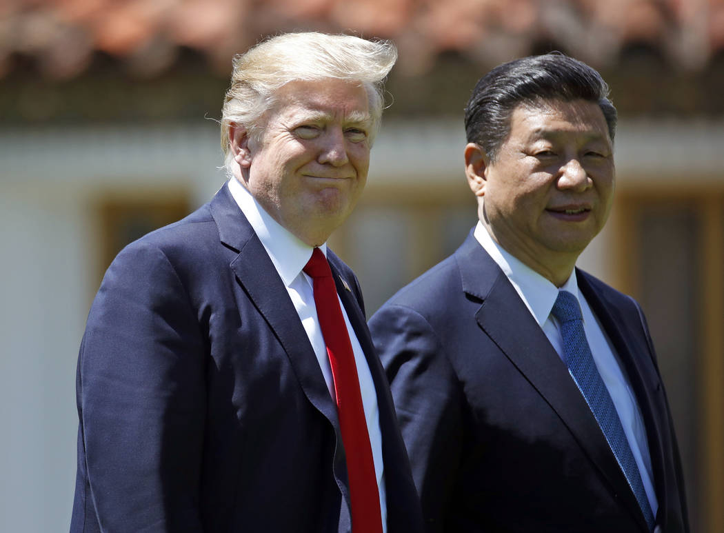 In this April 7, 2017, file photo President Donald Trump and Chinese President Xi Jinping walk together after their meetings at Mar-a-Lago in Palm Beach, Fla. Trump won cheers during the president ...