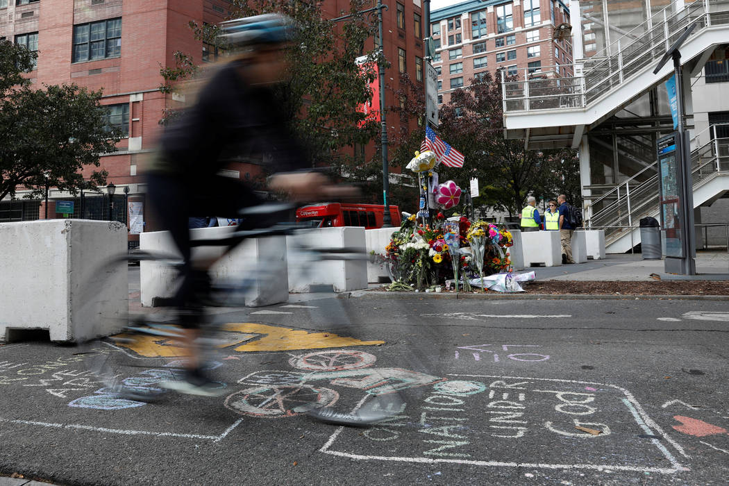 A bicyclist rides through newly placed barricades along a bike path next to a previous roadside memorial that is now being used to remember victims of Tuesday's attack at Chambers Street in New Yo ...