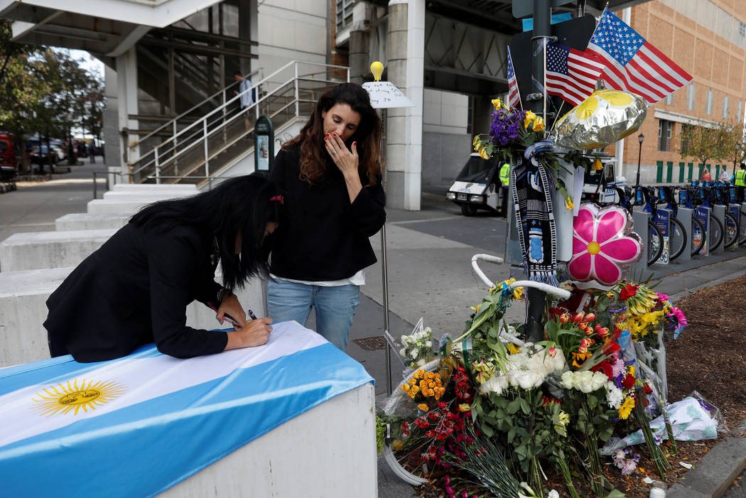 Albie Alvarez Coty (L) signs the flag of Argentina with Maria Lavilla on newly placed barricades along a bike path by a previous roadside memorial that is now being used to remember victims of Tue ...