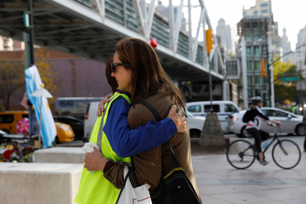 A woman is embraced by a grief councilor outside newly placed barricades along a bike path by a previous roadside memorial that is now being used to remember victims of Tuesday's attack at Chamber ...
