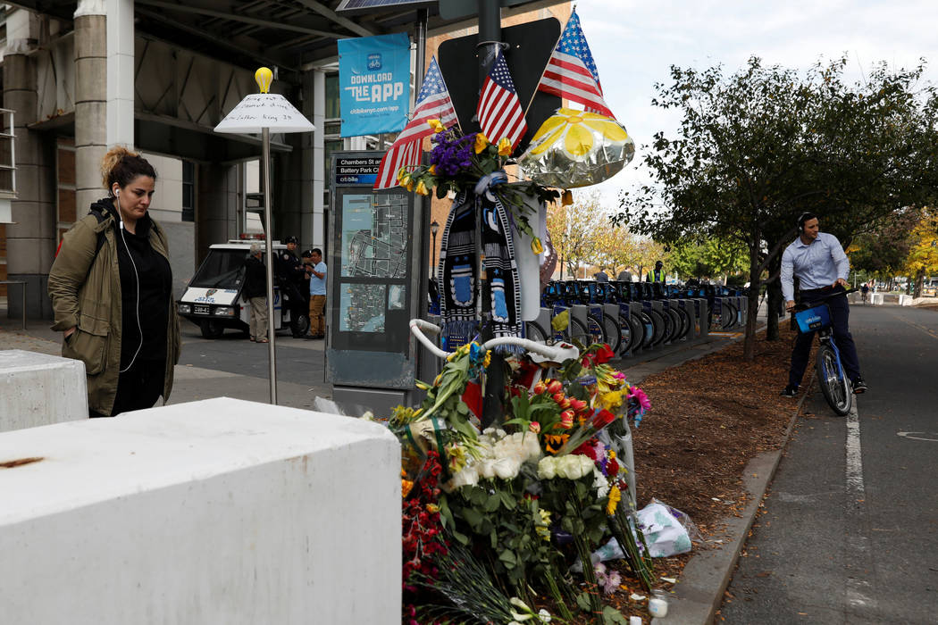 A woman stands next to newly placed barricades along a bike path by a previous roadside memorial that is now being used to remember victims of Tuesday's attack at Chambers Street in New York City, ...