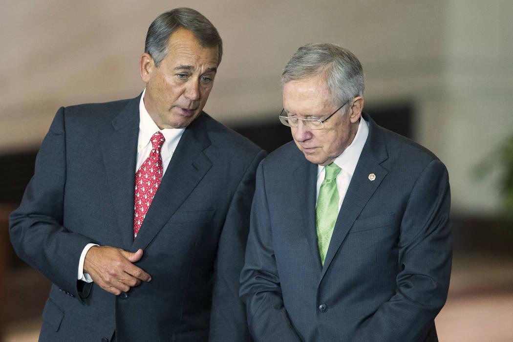 House Speaker John Boehner of Ohio, left, talks with Senate Majority Leader Sen. Harry Reid of Nev., right, on Capitol Hill in Washington, Wednesday, Dec. 10, 2014. (AP Photo/Evan Vucci)