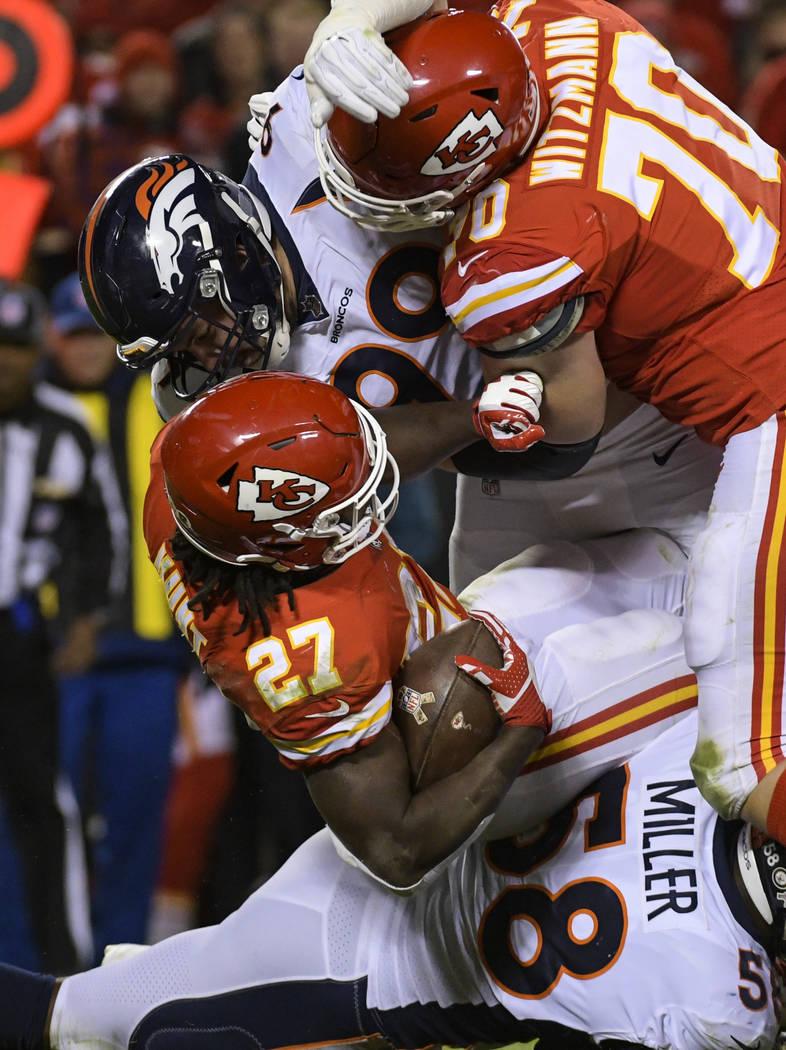 Kansas City Chiefs running back Kareem Hunt (27) is tackled by Denver Broncos defensive end Adam Gotsis (99) and Denver Broncos outside linebacker Von Miller (58) as Kansas City Chiefs offensive g ...