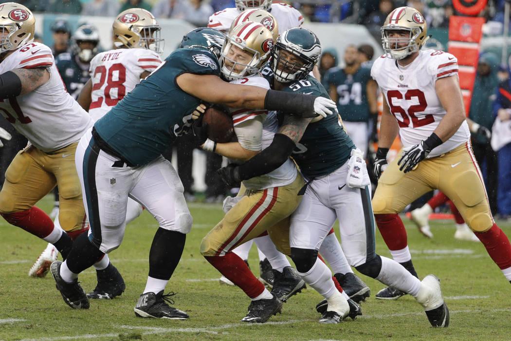 San Francisco 49ers quarterback C.J. Beathard, center, gets sandwiched between Philadelphia Eagles defensive tackle Destiny Vaeao, left, and defensive end Chris Long, right, during an NFL football ...