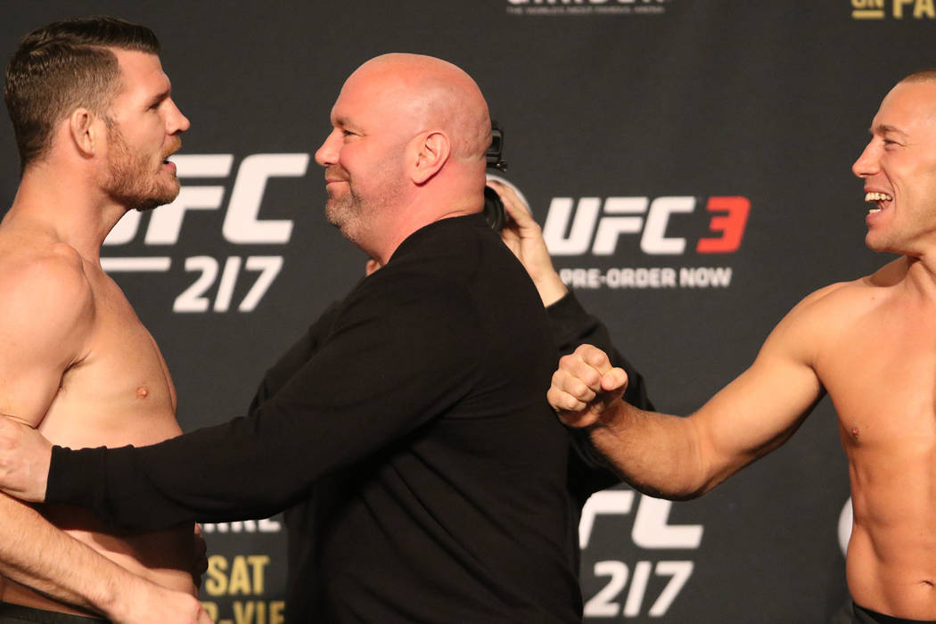 Georges St-Pierre, left, and UFC middleweight champion Michael Bisping face off at the UFC 217 ceremonial weigh-in at the Madison Square Garden theater in New York, New York, Friday, Nov. 3, 2017. ...