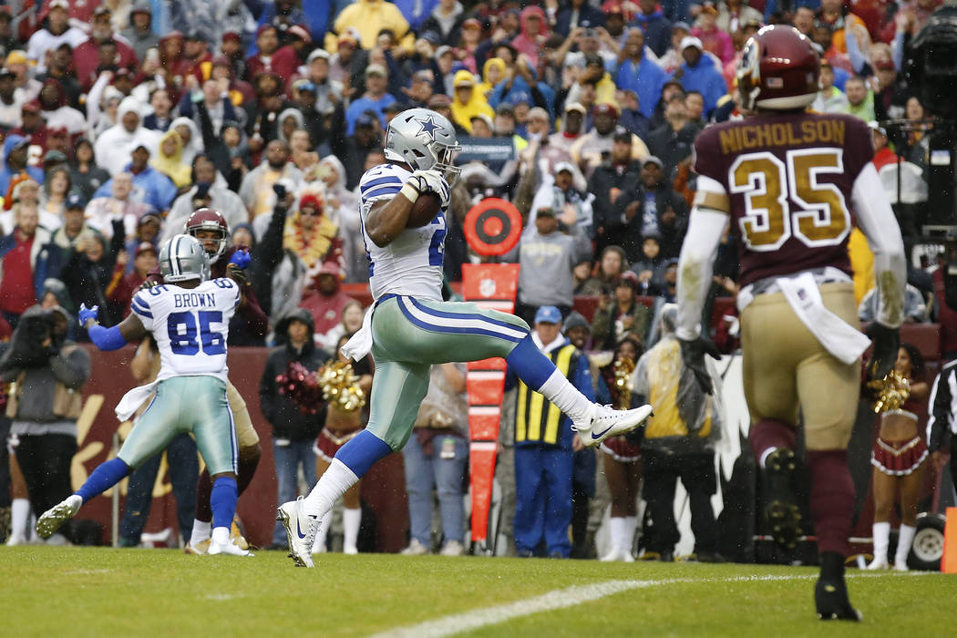 Dallas Cowboys running back Ezekiel Elliott (21) jumps across the goal line as he scores a touchdown during the first half of an NFL football game against the Washington Redskins in Landover, Md., ...
