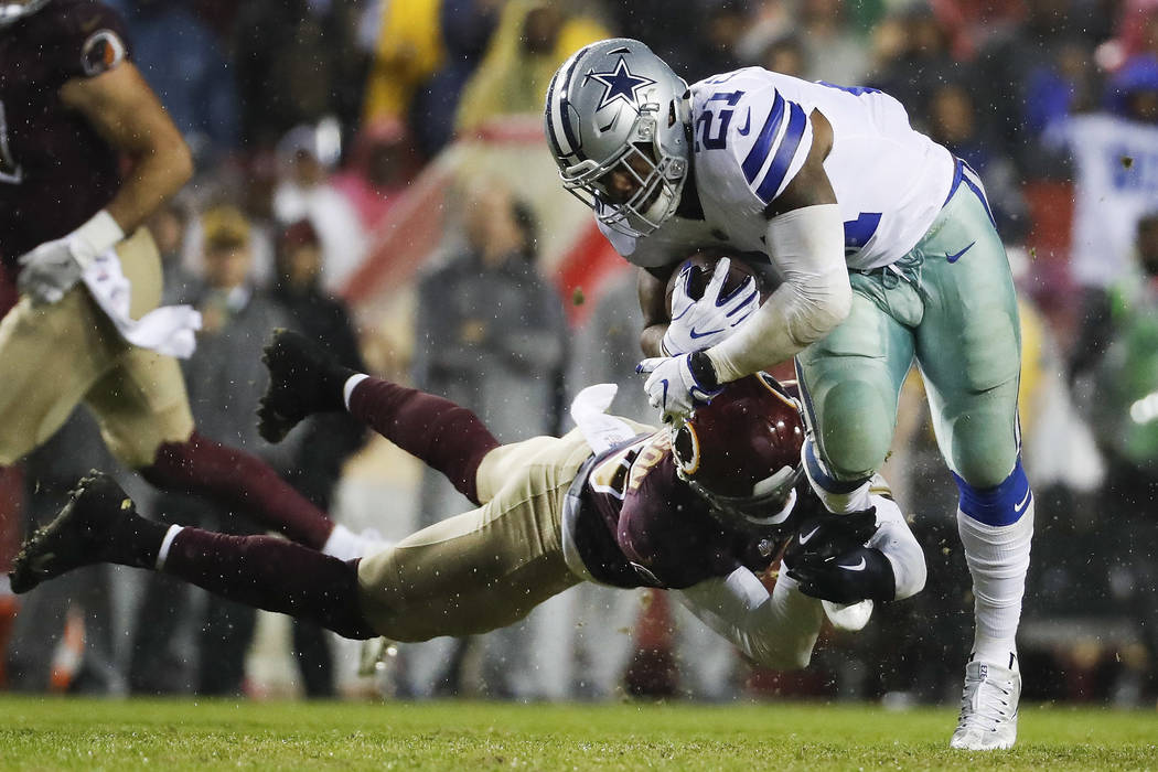 Washington Redskins strong safety Montae Nicholson (35) hangs unto Dallas Cowboys running back Ezekiel Elliott (21) during the second half of an NFL football game in Landover, Md., Sunday, Oct. 29 ...