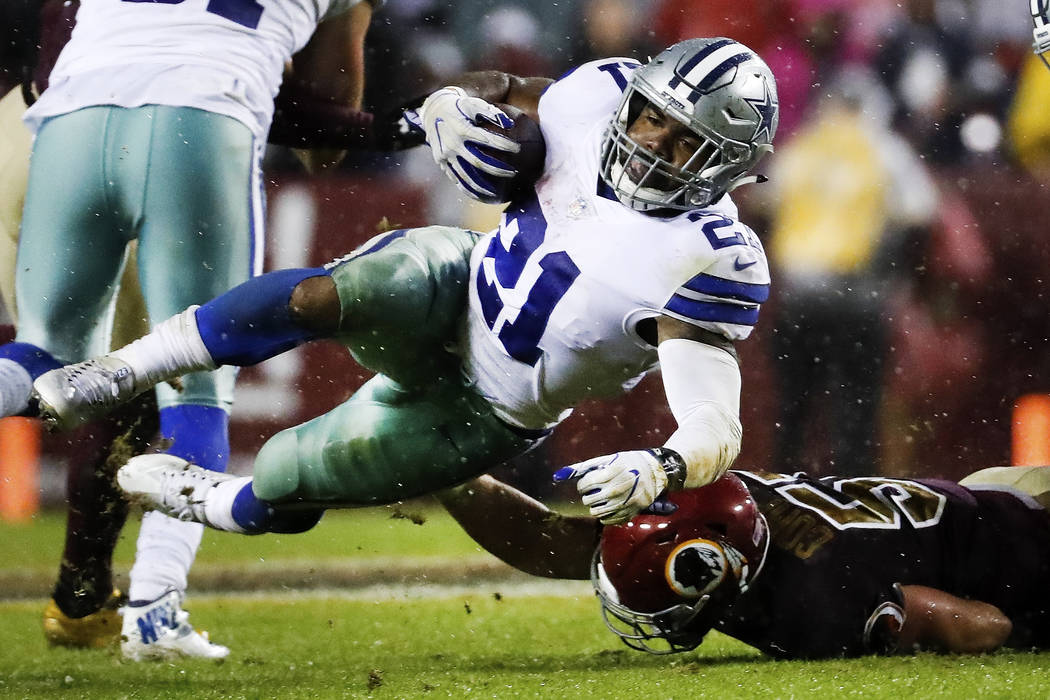 Dallas Cowboys running back Ezekiel Elliott (21) is knocked off his feet by Washington Redskins inside linebacker Will Compton (51) during the second half of an NFL football game in Landover, Md., ...