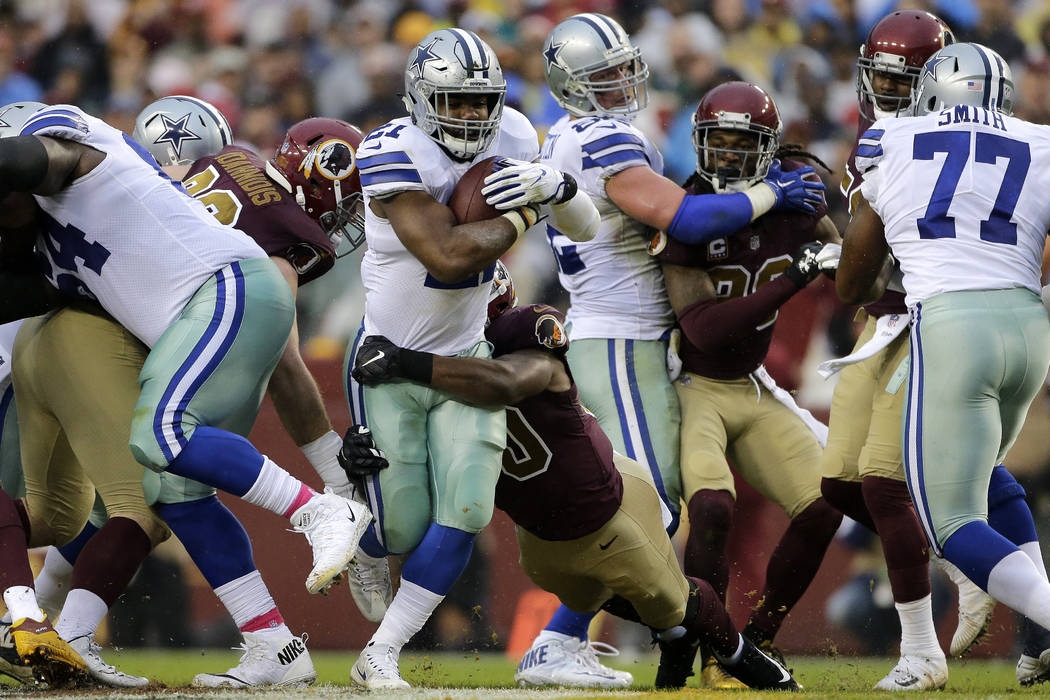 Dallas Cowboys running back Ezekiel Elliott, center, runs the ball during an NFL football game against the Washington Redskins, Sunday, Oct. 29, 2017, in Landover, Md. (AP Photo/Mark Tenally)