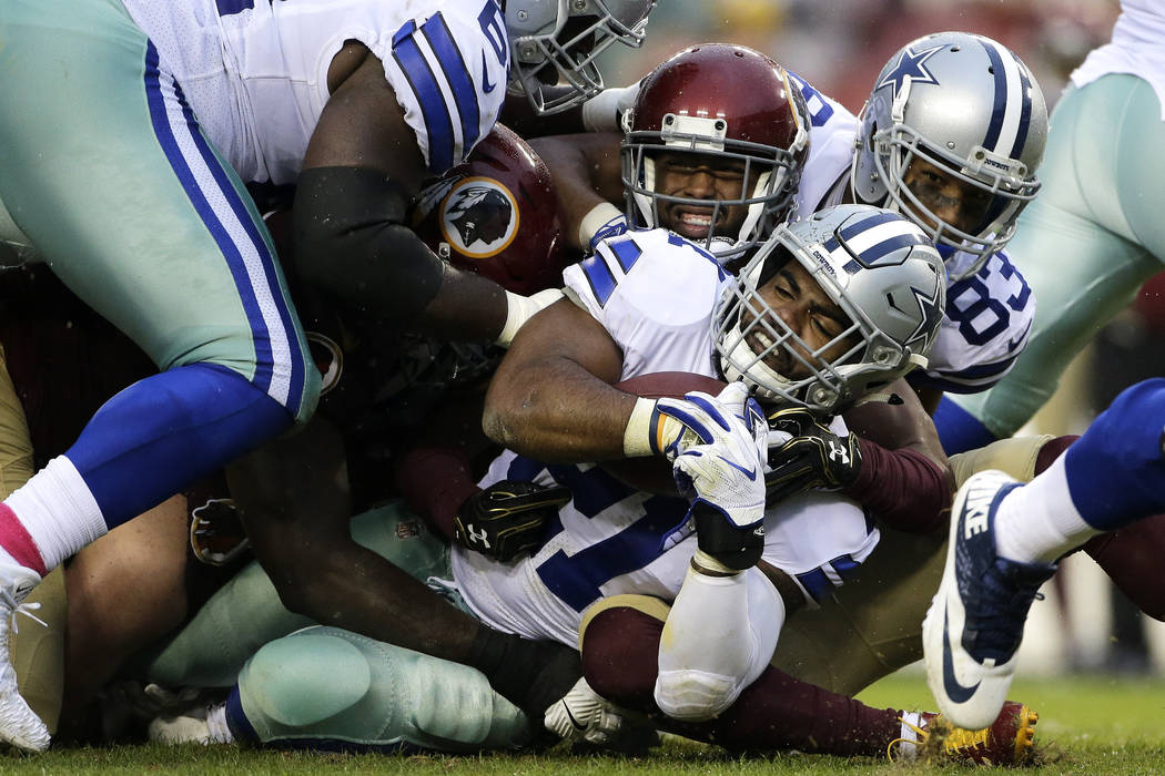 Dallas Cowboys running back Ezekiel Elliott, center, is tackled during an NFL football game against the Washington Redskins, Sunday, Oct. 29, 2017, in Landover, Md. (AP Photo/Mark Tenally)
