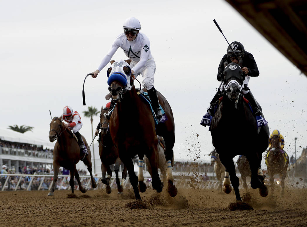 Jockey Flavien Prat, center, celebrates aboard Battle of Midway after beating second-place Sharp Azteca, ridden by jockey Paco Lopez, in the Las Vegas Dirt Mile horse race during the first day of  ...