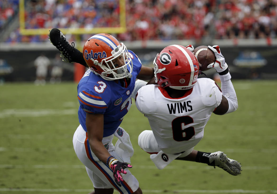 Georgia wide receiver Javon Wims (6) catches a pass in for a touchdown over Florida cornerback Marco Wilson (3) in the first half of an NCAA college football game, Saturday, Oct. 28, 2017, in Jack ...