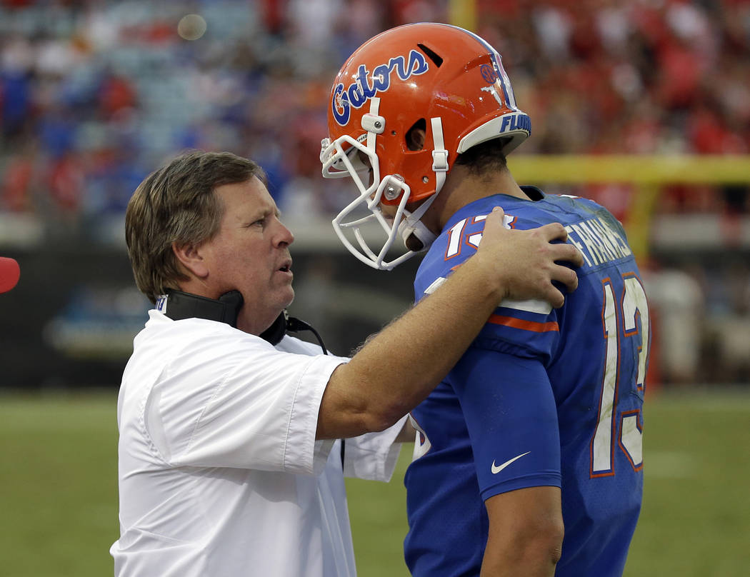 Florida head coach Jim McElwain talks with quarterback Feleipe Franks (13) on the sideline in the second half of an NCAA college football game against Georgia, Saturday, Oct. 28, 2017, in Jacksonv ...
