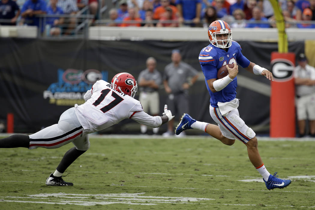 Florida quarterback Feleipe Franks (13) scrambles away from Georgia linebacker Davin Bellamy (17) in the first half of an NCAA college football game, Saturday, Oct. 28, 2017, in Jacksonville, Fla. ...