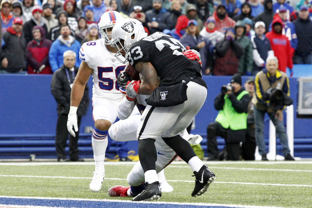 Oakland Raiders running back DeAndre Washington (33) scores a touchdown catch on a pass from quarterback Derek Carr, not pictured, as Buffalo Bills middle linebacker Preston Brown (52) tries to ma ...