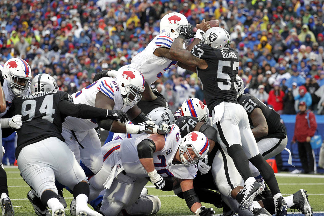 Buffalo Bills quarterback Tyrod Taylor, top right, leaps in for a touchdown as Oakland Raiders middle linebacker NaVorro Bowman (53) tries to stop him during the second half of an NFL football gam ...