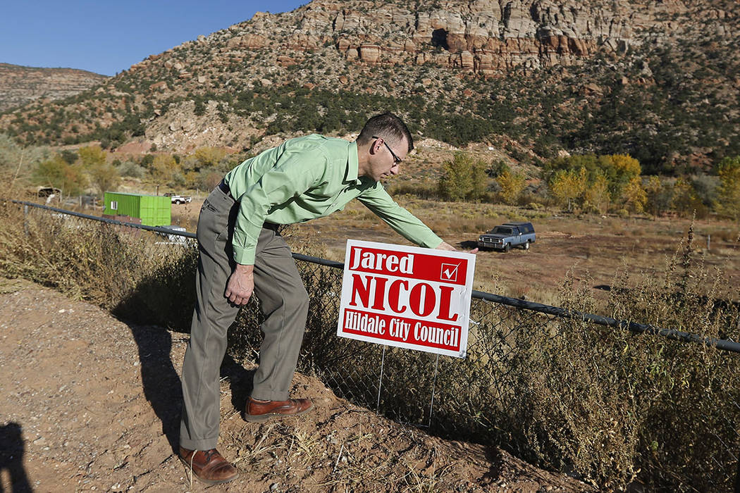 Jared Nicol plants his campaign sign for city council in Hildale, Utah, last month. Nicol, a member of the mainstream Mormon church, moved to the rural community for a better life for his two chil ...