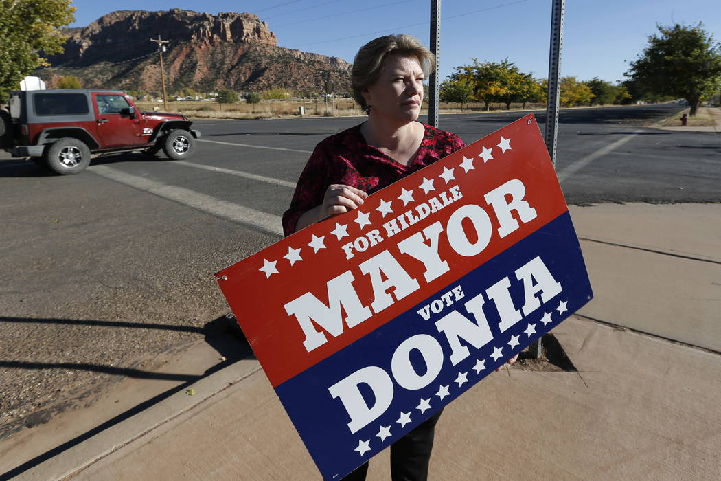 Donia Jessop holds her mayoral campaign sign outside her store in Colorado City, Ariz., last month. (AP Photo/Rick Bowmer)