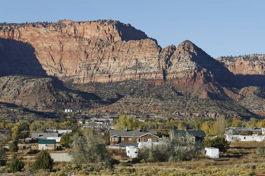 Hildale, Utah, is seen at the base of Red Rock Cliff mountains, with its sister city, Colorado City, Ariz., in the foreground. (AP Photo/Rick Bowmer)