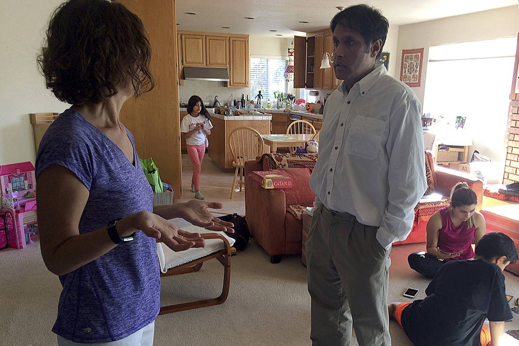 Lucia Cascio, left, talks with her husband Raj Sodhi in the living room of a friend's home in Santa Rosa, Calif., last month. (AP Photo/Sudhin Thanawala)