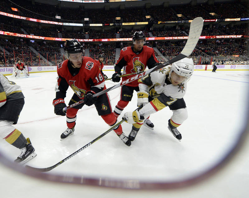 Nov 4, 2017; Ottawa, Ontario, CAN; Ottawa Senators forward Ryan Dzingel (18) and teammate Cody Ceci (5) and Vegas golden Knights forward William Karlsson (71) battle for the puck along the boards  ...
