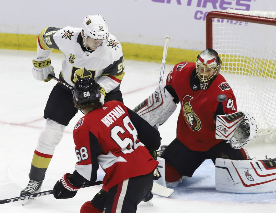 Vegas Golden Knights left wing Tomas Nosek (92) and Ottawa Senators goalie Craig Anderson (41) keep their eyes on a flying puck as left wing Mike Hoffman (68) looks on during the first period of a ...