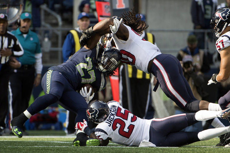 Oct 29, 2017; Seattle, WA, USA; Seattle Seahawks running back Eddie Lacy (27) is tackled by Houston Texans cornerback Kareem Jackson (25) and outside linebacker Jadeveon Clowney (90) during the fi ...