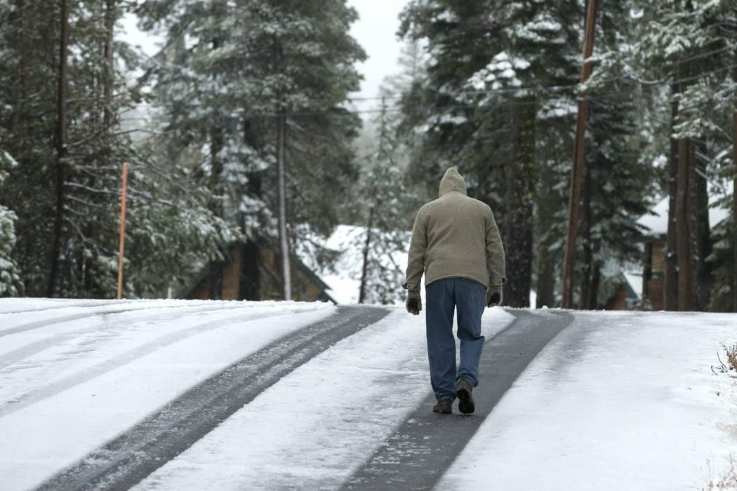 A man walks a snow covered road near Soda Springs, Calif., Friday, Nov. 3, 2017. (AP Photo/Rich Pedroncelli)