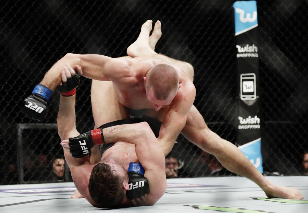Georges St-Pierre, of Canada, above, fights England's Michael Bisping during a middleweight title mixed martial arts bout at UFC 217 Sunday, Nov. 5, 2017, in New York. St-Pierre won the fight. (AP ...