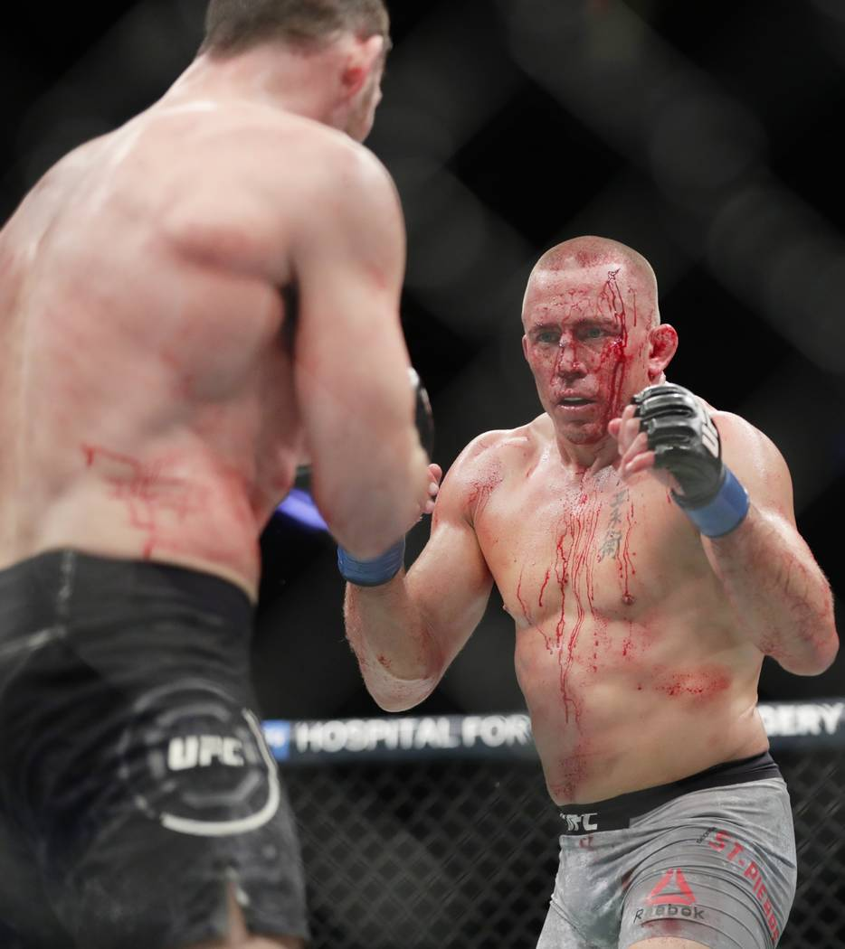 Georges St-Pierre, right, of Canada, faces England's Michael Bisping, during a middleweight title mixed martial arts bout at UFC 217 early Sunday, Nov. 5, 2017, in New York. St-Pierre won the figh ...