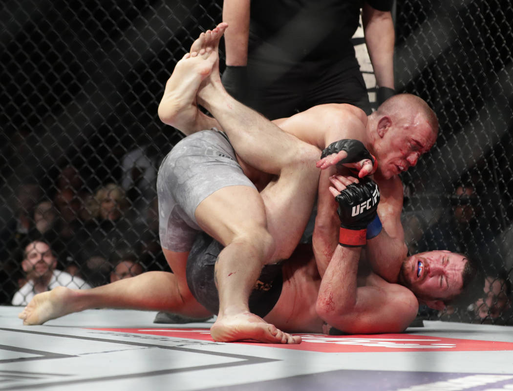 Georges St-Pierre, above, of Canada, fights England's Michael Bisping during a middleweight title mixed martial arts bout at UFC 217 Sunday, Nov. 5, 2017, in New York. St-Pierre won the fight. (AP ...