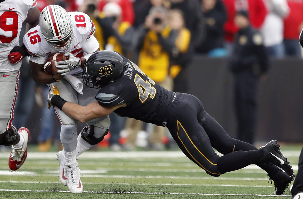Ohio State quarterback J.T. Barrett (16) is tackled by Iowa linebacker Josey Jewell during the first half of an NCAA college football game, Saturday, Nov. 4, 2017, in Iowa City, Iowa. (AP Photo/Ch ...